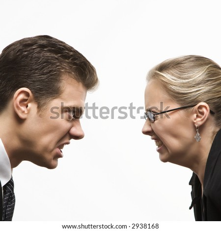 Close-up of Caucasian mid-adult man and woman staring at each other with hostile expressions. - stock photo