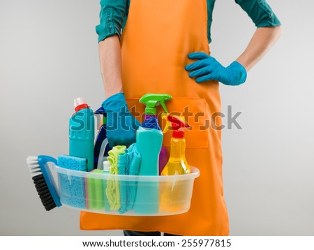 close-up of caucasian woman holding basin with cleaning supplies - stock photo