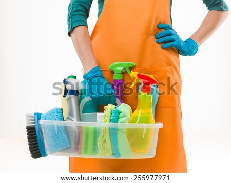 close-up of caucasian woman holdinh basin with cleaning supplies, on white background - stock photo