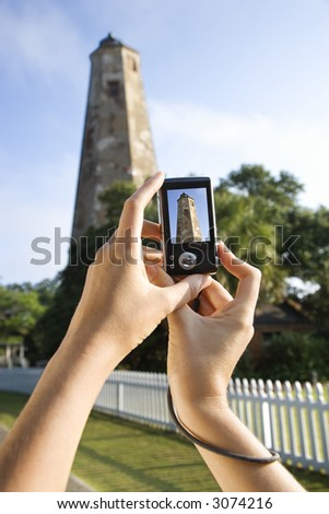 Close up of Caucasian woman's hands holding digital camera and photographing lighthouse at Bald Head Island, North Carolina. - stock photo