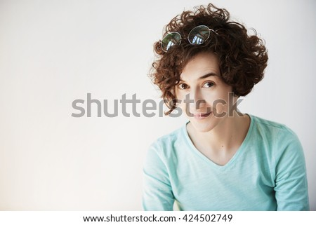 Close up of Caucasian woman with curly hair looking in surprise at the camera with shy and mysterious smile, posing against white studio wall with copy space for your text or advertising content - stock photo