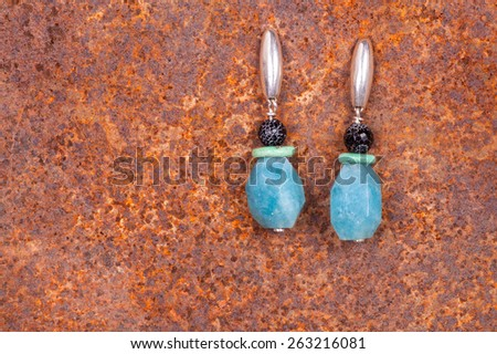 Close up of chalcedony earrings on rusty iron, manufactured by Ornella Salamone - stock photo