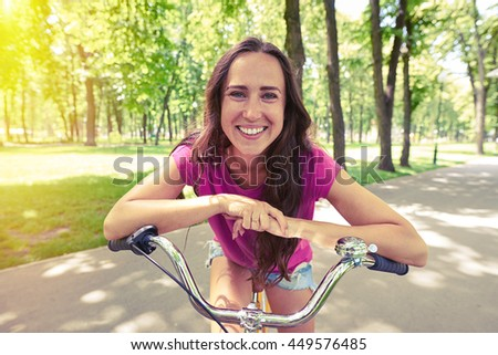 Close-up of charming smiling lady posing with hands resting on handlebar of the bicycle in the park  - stock photo