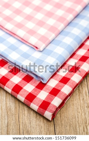 Close up of checkered cloths on a table of wood