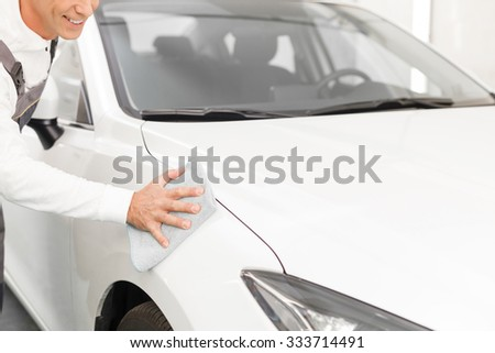 Close up of cheerful male mechanic cleaning a white car with cloth. The man is standing in uniform and smiling - stock photo