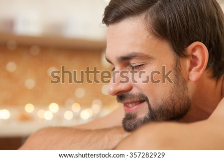 Close up of cheerful man relaxing at massage salon. He is smiling with closed eyes. The man is lying with joy