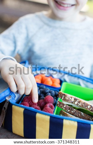 close-up of cheerful schoolboy eating healthy lunch outdoor - stock photo
