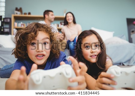 Close-up of cheerful siblings with controllers playing video game on carpet at home - stock photo