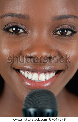 Close up of cheerful smiling female singer with microphone - stock photo