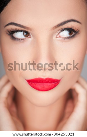 Close up of cheerful woman is looking aside flirtingly. She is touching her skin and gently smiling - stock photo