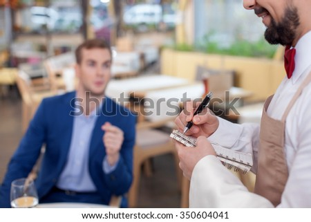 Close up of cheerful young cafe worker serving a male customer. He is standing and noting. The man is smiling. The businessman is sitting and talking  - stock photo