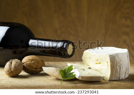 Close-up of cheese and walnuts on wood board - stock photo