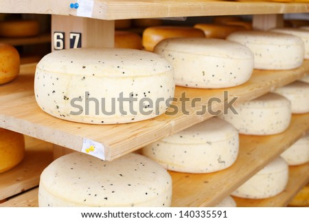 Close up of cheese ripening on wooden shelves - stock photo