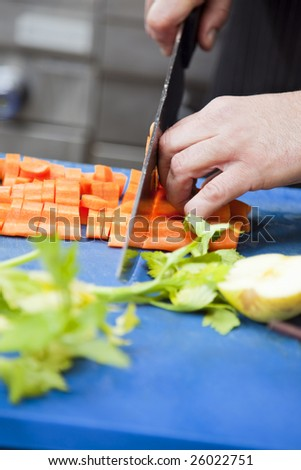 close-up of chef cutting some carrots on blue cutting board - stock photo