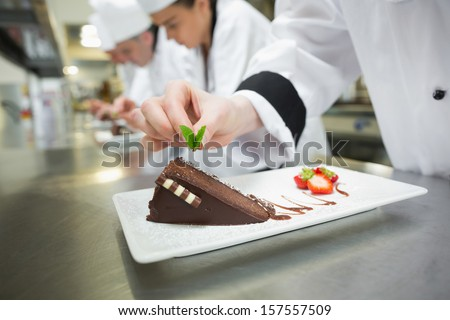 Close up of chef putting mint leaf on chocolate cake in busy kitchen - stock photo