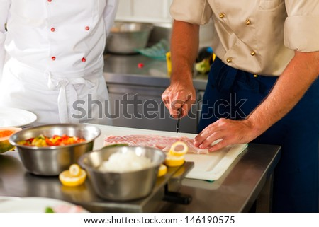 Close up of chefs in a commercial restaurant or hotel kitchen working, they are preparing an fish fillet and vegetables - stock photo