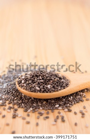 Close up of Chia seeds in a wooden spoon on the table - stock photo