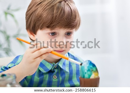 Close up of child coloring easter egg - stock photo