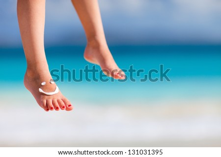 Close up of child feet with smile made with sun cream - stock photo