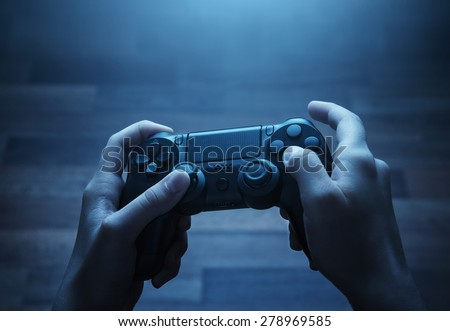 Close up of child hands playing the video game at night - stock photo