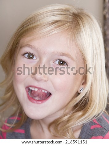Close up of child missing her top front tooth touching it with her tongue