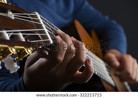 Close up of child playing classical guitar. - stock photo