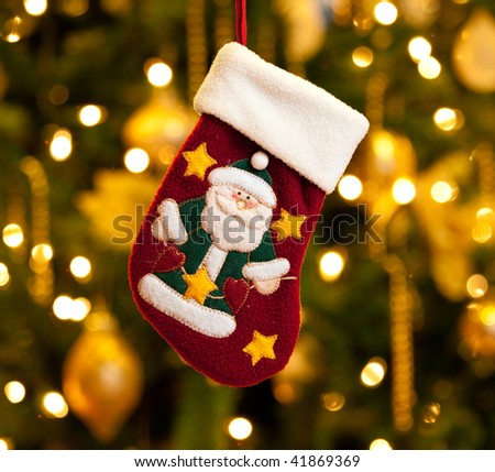 Close up of child's christmas stocking in front of out of focus Christmas tree - stock photo