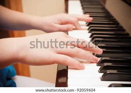 Close up of child's hands playing the piano - stock photo