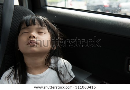 Close up of child sleeping in the car without seat belt - stock photo