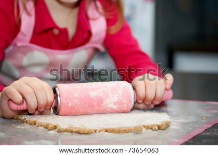 Close-up of child with a rolling pin baking cookies - stock photo