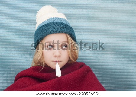 Close up of child with fever thermometer, wrapped in blanket, Space for text - stock photo