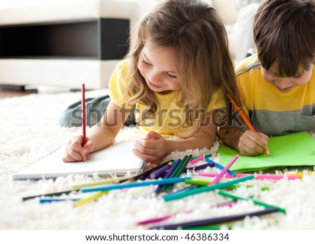 Close-up of children drawing lying on the floor in the living room - stock photo
