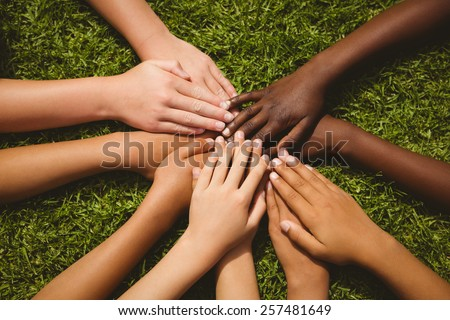 Close up of children keeping hands together over grass - stock photo
