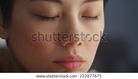 Close up of Chinese woman resting with eyes closed - stock photo