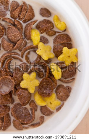 Close-up of Chocolate and star colorful children cereal and milk on a bowl isolated  - stock photo
