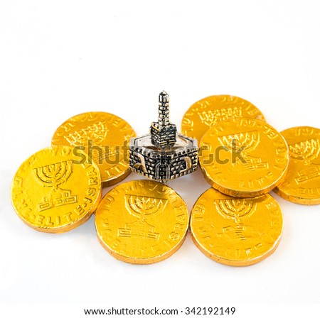 Close up of chocolate coins and silver dreidel for Hanukkah celebration. - stock photo