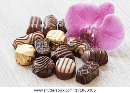 close up of chocolate confectionery on desk with orchid - stock photo