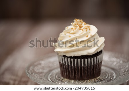 close up of chocolate cupcake with vanilla frosting on antique glass plate - stock photo