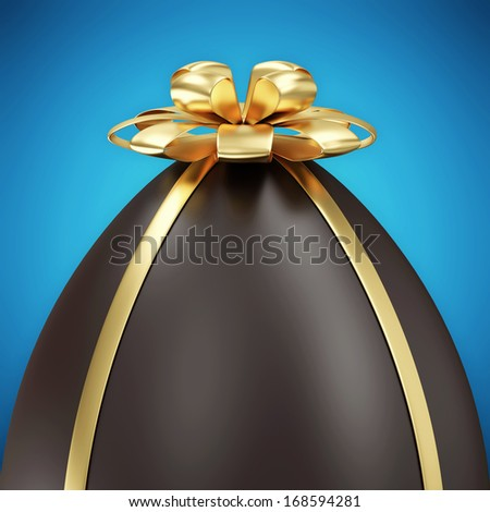 Close-up of Chocolate Easter Egg with Golden Bow on blue background