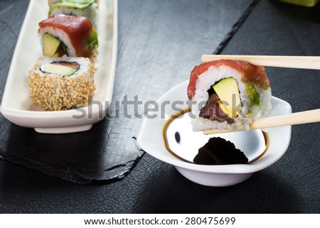 close up of chopsticks taking portion of sushi over a bowl of soy sauce / eating sushi rolls  - stock photo