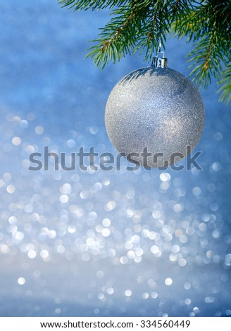 Close up of Christmas ball on a Christmas tree branch over blurred shiny background. Selective focus.