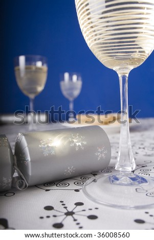 Close up of Christmas crackers, glasses of wine and mince pies on a dining table with blue wall background. - stock photo
