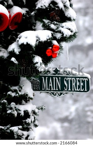 close up of christmas decorated street pole covered in snow with Main Street cast sign - stock photo