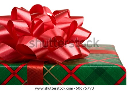 Close up of Christmas gift box wrapped in red and green plaid paper with a bow on top. - stock photo