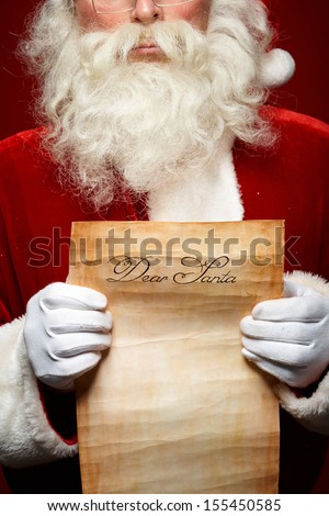 Close-up of Christmas letter in Santa Claus hands - stock photo