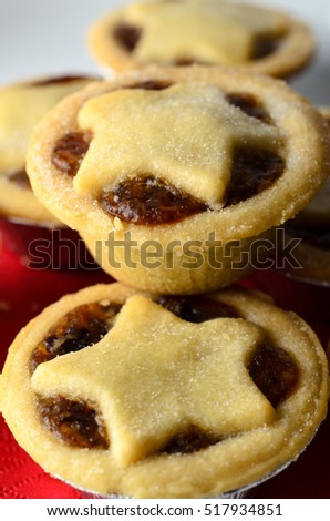 Close up of Christmas mince pies with star shaped pastry toppers, piled on a white plate with crumbs; a red napkin.