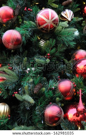 Close up of christmas ornaments on tree - stock photo