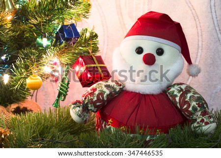 Close up of Christmas Santa claus fabric craft and decorated hanging on the Christmas tree against the white curtain - stock photo