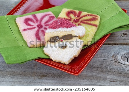 Close up of Christmas sugar cookies on green napkin and red plate with rustic wood underneath