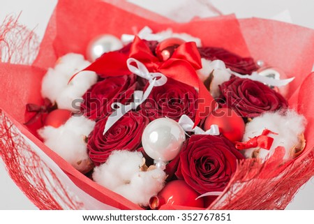 Close-up of Christmas winter bouquet of red rose and cotton in the package. shallow DOF